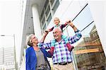 Granddaughter sitting on senior man's shoulders in city