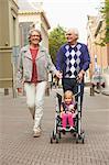 Senior couple pushing granddaughter in baby stroller