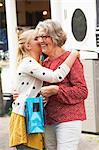 Teenage girl embracing grandmother in street