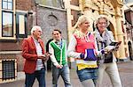 Grandparents and teenage grandchildren walking in city