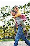 Teenager-Mädchen haben eine huckepack Fahrt vom jungen Mann im park