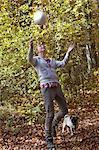 Mädchen spielen mit Fußball im Wald
