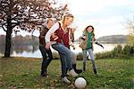 Girls playing soccer next to lake