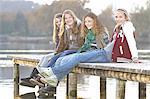 Girls sitting together on lake pier, portrait