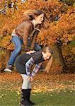 Girl leapfrogging over friend in park