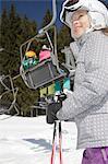 Girl holding ski poles under ski lift