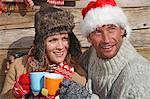 Couple enjoying hot drink outside cabin at ski resort