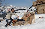 Mature man throwing snowball at woman on wooden chair at ski resort