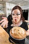 Frau machen lustige Gesichtsausdrücke und hielt Apfelkuchen in Bäckerei