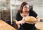 Frau mit aufgeregt Gesichtsausdruck Apfelkuchen in Bäckerei Küche hält