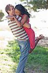 Man lifting girlfriend outdoors