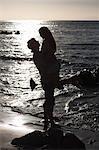Man lifting girlfriend on beach