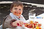 Toddler boy eating pasta outdoors