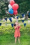 Girl holding bouquet de ballons à l'extérieur