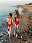 Girls walking on rocky beach