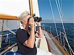 Ältere Frau mit Fernglas auf Segelboot