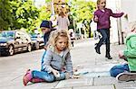 Children drawing on sidewalk with chalk