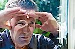 Man peering in window of house