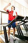 Eau potable sur tapis roulant à la gym homme