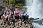 Children sitting on rock by waterfall