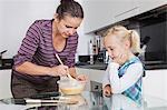 Fille regardant la mère de cuisson dans la cuisine