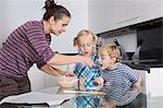 Mes enfants, cuisson et dégustation de pâte de cookie dans la cuisine