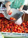 Personne pesant les tomates au marché des fermiers.