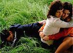 Femme, étreindre, homme étendu dans l'herbe