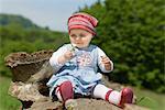 Femelle bébé assis sur une souche d'arbre avec pissenlit