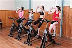 Women on exercise bikes, drinking from bottles