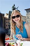 Young woman having salad at restaurant outdoors