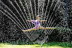 Ballerina leaping through a water sprinkler