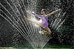 Ballerina jumping over water sprinkler