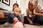 Vater, Mutter und Sohn indem Münzen in Sparschwein