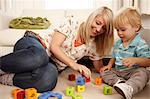 Mutter und Sohn spielen mit Alphabet-Blöcke