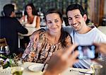 Happy young Friends posiert für Foto an Restaurant-Tisch mit Menschen im Hintergrund