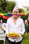 Porträt von glücklich Reifen Mann, der Teller voll von gekochten Hummer mit Freunden im Hintergrund hält
