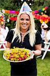 Portrait d'heureuse jeune femme tenant l'assiette pleine de homard cuit avec des amis en arrière-plan