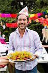 Portrait of happy Mitte erwachsenen Mann, der Teller voll von gekochten Hummer mit Freunden im Hintergrund hält