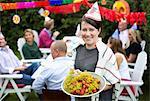 Portrait of happy Woman hält Teller mit gekochten Hummer mit Freunden im Hintergrund