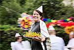 Porträt der Frau mittleren Alters hält Teller mit gekochten Hummer mit Freunden im Hintergrund