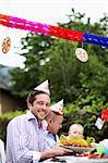 Portrait of happy Mitte erwachsener Mann, hält Teller mit Hummer mit Freund und Kind im Hintergrund