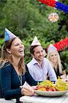 Glückliche junge Frau mit Freunden am Esstisch Kräftskiva feiert