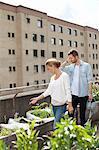 Jeune couple de race blanche examinant les plantes au jardin urbain
