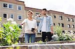 Jeune couple examinant les plantes au jardin urbain