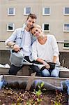 Portrait de jeune homme tenant arrosoir assis avec une femme au jardin urbain