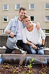 Heureux jeune homme tenant arrosoir assis avec une femme au jardin urbain