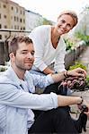 Heureux jeune couple tenant les légumes fraîchement récoltés au jardin urbain
