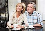 Glückliches Paar beim Kaffee beim Wegsehen am Tisch