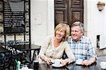 Glückliches Paar Wegsehen, während beim Kaffee am Tisch